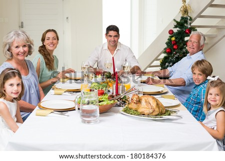 Happy multigeneration family having Christmas meal together at dining table - stock photo