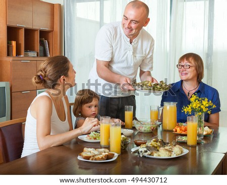 Happy multigeneration family together over healthy dining table at home interior
