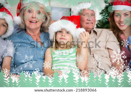 Happy multigeneration family wearing santa hats on the couch against snowflakes and fir trees in green - stock photo