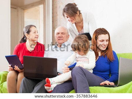 Happy multigenerations family   in  room with laptops