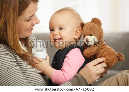 Happy mum and baby girl laughing cuddling holding teddy bear. - stock photo