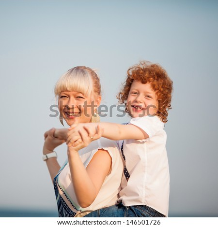 happy mum and her red head son having fun together outside, close up - stock photo