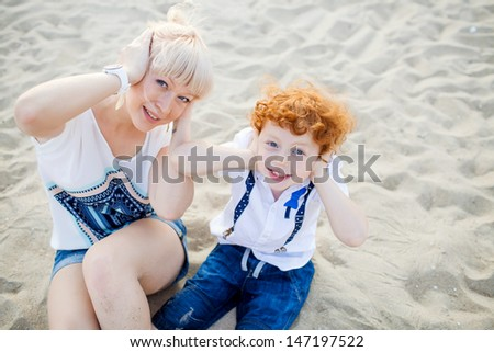 happy mum and her red head son having fun together outside on the beach - stock photo