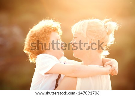 happy mum and her red head son having fun together outside on the beach, close up - stock photo