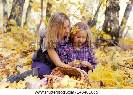 Happy mum and the daughter play autumn park on the fallen down foliage
