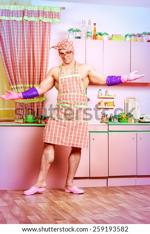 Happy muscular man in an apron standing in the pink kitchen. Love concept. Valentine's day. Women's day.  - stock photo