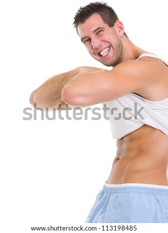 Happy muscular man raising shirt to show abdominal muscles