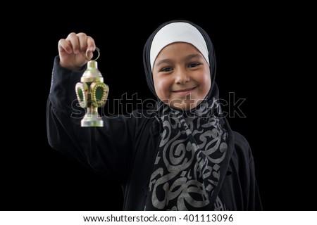 Happy Muslim Girl Smiling with Ramadan Lantern over Black Background - stock photo