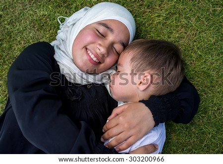 Happy Muslim mother and kid in nature - stock photo