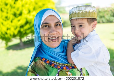 Happy Muslim mother and kid in nature