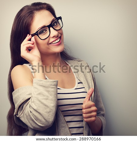 Happy natural smiling young woman in glasses showing thumb up. Closeup vintage portrait - stock photo