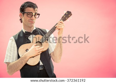 Happy nerd man with glasses play music with ukulele guitar