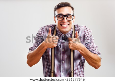 Happy nerdy man is showing thumbs up.Nerdy man giving thumbs up - stock photo