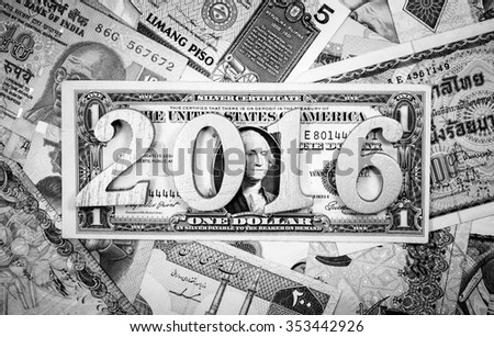 Happy new year and hope to be rich with wooden number 2016 put on one american dollar and many currency,banknote on black and white color - stock photo