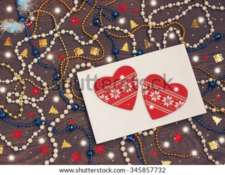 Happy New year and Merry Christmas! New Year's background. New Year's congratulation,  decorative jewelry in the form of heart on an envelope, a color beads and confetti on a  table. Card, invitation. - stock photo