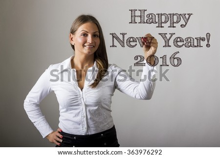 Happy New Year 2016 - Beautiful girl writing on transparent surface - horizontal image