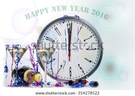 Happy new year champagne celebration showing a clock at midnight with glasses and party poppers - stock photo