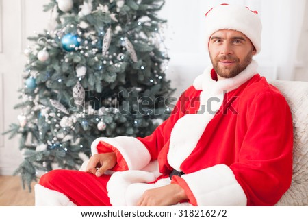 Happy New Year. Cheerful young Santa Claus is sitting in chair near fir-tree. He is looking at the camera and smiling - stock photo