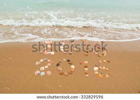 Happy New Year 2016 concept: The waves are about to cover 2015, both years placed with seashells on the beach - stock photo