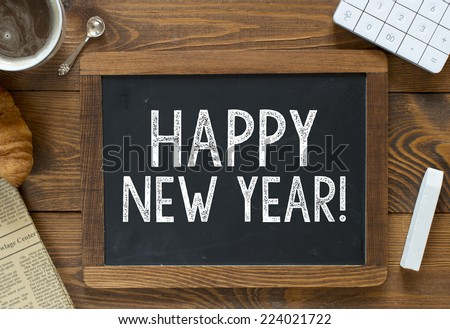 Happy New Year! handwritten with white chalk on a blackboard on a wooden background - stock photo