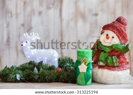 Happy New Year. Holiday toy snowman, candle and bear are situated near pine wreath