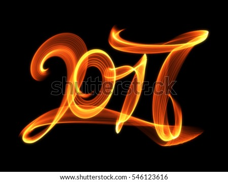 Happy new year 2017 isolated numbers lettering written with fire flame or smoke on black background.