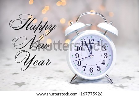 Happy New Year message with white retro clock showing five to midnight on white starry background with bokeh Christmas lights. - stock photo