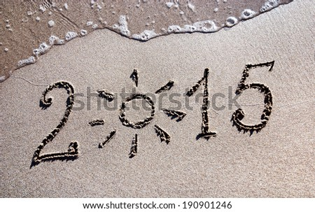 Happy New Year 2015 on the sea sand beach with the sun rays and wave