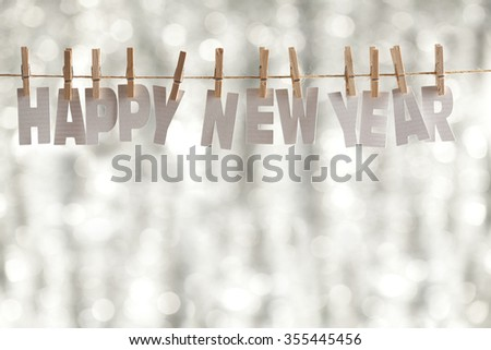 Happy new year - paper letters on bokeh background - stock photo