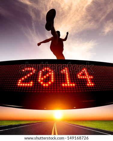 happy new year 2014.runner jumping and crossing over matrix display for celebrating 2014 - stock photo