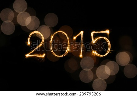 Happy New Year 2015 sparkle firework writing with dirty gold colorful lights blur bokeh background  - stock photo