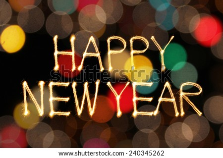 Happy New Year sparkle firework writing with unfocused dirty colorful light blur bokeh background - stock photo