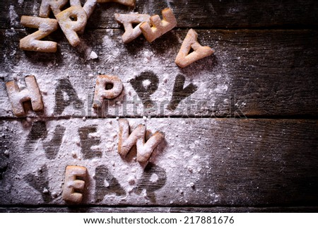Happy New Year text with cookies and blank space on the wooden background - stock photo