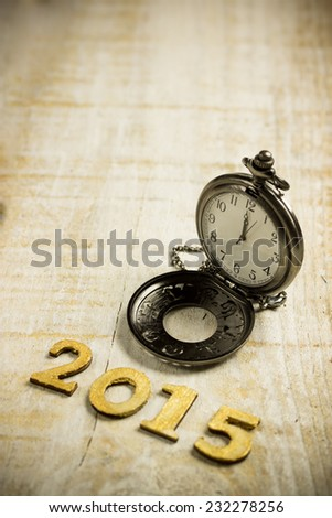 Happy New Year 2015! Vintage watch on a wooden background showing twelve. - stock photo