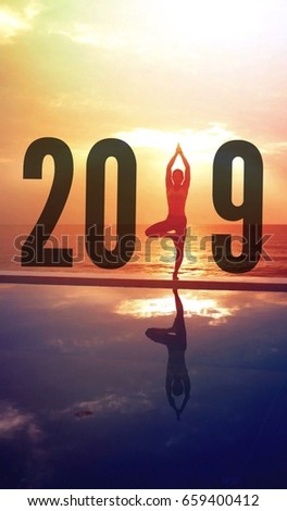 Happy new year 2019 woman practice yoga on the beach sunrise