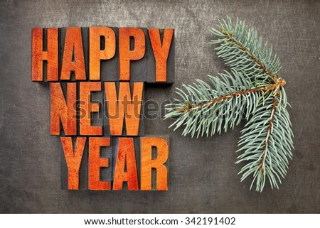 Happy New Year! - word abstract in vintage letterpress wood type blocks stained by red ink on a grunge metal background with a branch of Colorado silver spruce - stock photo