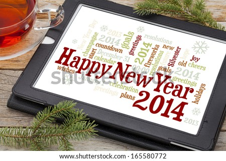 Happy New Year 2014 - word cloud on a digital tablet with a cup of tea and spruce twigs - stock photo