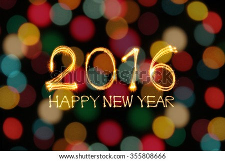 Happy New year 2016 written by sparklers firework with blurred gold lights bokeh background - stock photo