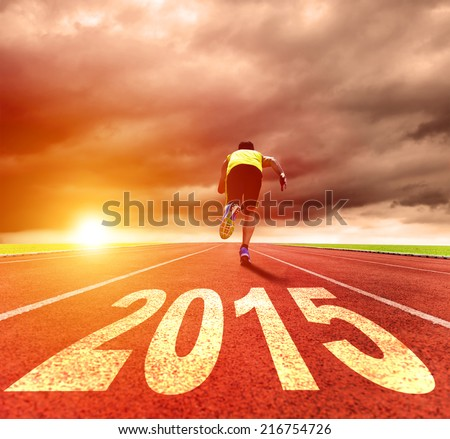 happy new year 2015. young man running with sunrise background - stock photo