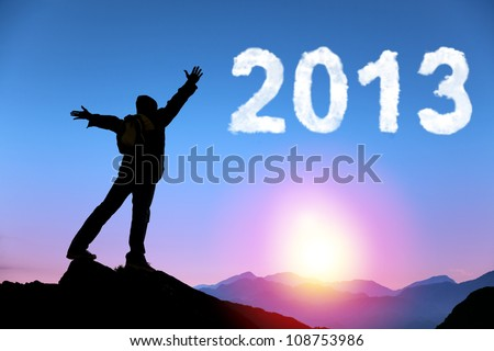 happy new year 2013. young man standing on the top of mountain watching the sunrise and cloud 2013 - stock photo
