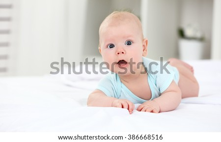 happy newborn baby on the bed at home