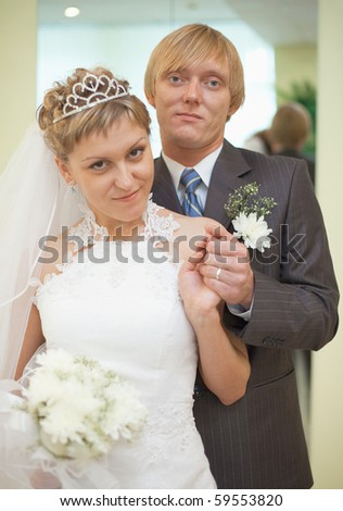 Happy newly-married couple - a smart portrait in a solemn hall - stock photo