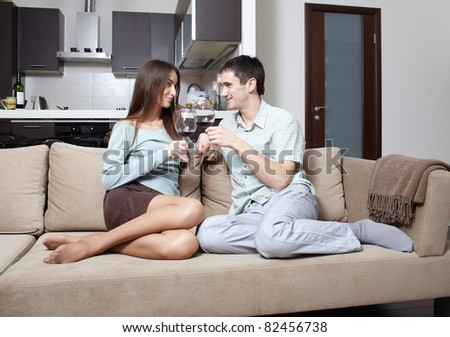 Happy newly married couple at home on sofa - stock photo