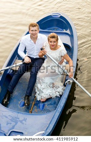 Happy newly married couple riding on rowing boat at evening - stock photo