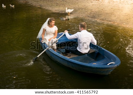 Happy newly married couple riding on rowing boat on lake - stock photo