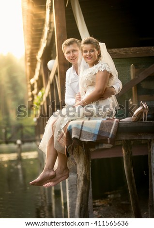 Happy newly married couple sitting on old wooden pier at sunny day - stock photo