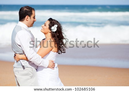 happy newlywed couple hugging on beach