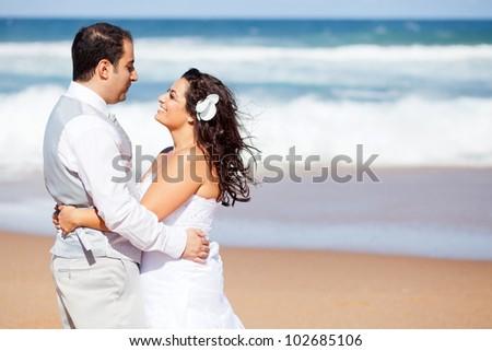 happy newlywed couple hugging on beach - stock photo