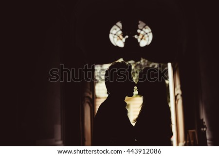 Happy newlyweds are kissing indoor. Bride and groom stand near the window. Silhouette of happy family - stock photo