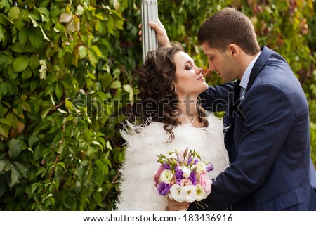 Happy newlyweds in park. Portrait of loving young bride and groom. - stock photo